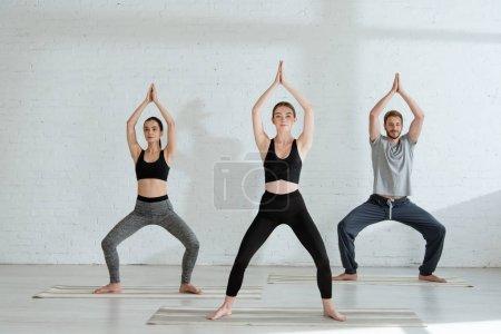 Photo pour Jeunes hommes et femmes pratiquant le yoga dans la pose de la déesse avec des mains de prière élevées - image libre de droit