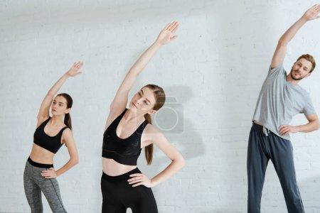 Photo pour Jeunes en vêtements de sport faisant inclinaison latérale dans la pose de montagne avec la main sur la hanche - image libre de droit