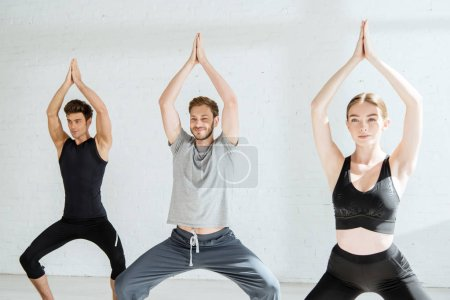 Photo for Young men and woman practicing yoga in goddess pose with raised prayer hands - Royalty Free Image