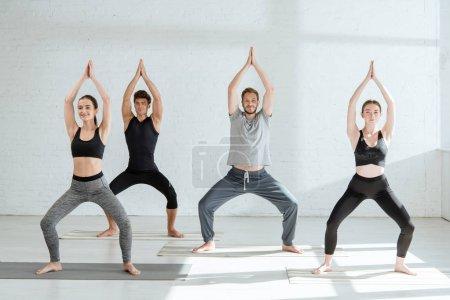 Photo pour Jeunes en vêtements de sport pratiquant le yoga dans la pose de la déesse avec des mains de prière levées - image libre de droit