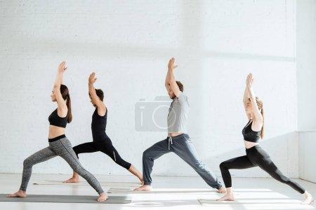 Photo pour Vu de côté des jeunes dans les vêtements de sport pratiquant le yoga en guerrier je pose - image libre de droit