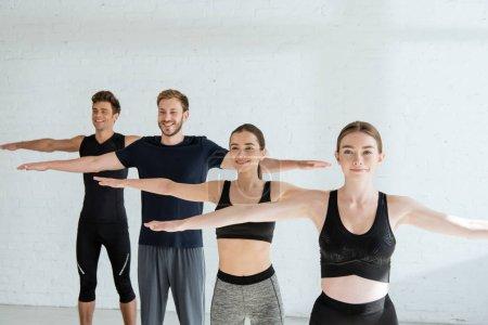 Photo pour Les jeunes souriants en vêtements de sport pratiquant le yoga dans la pose à bras ouverts de montagne - image libre de droit