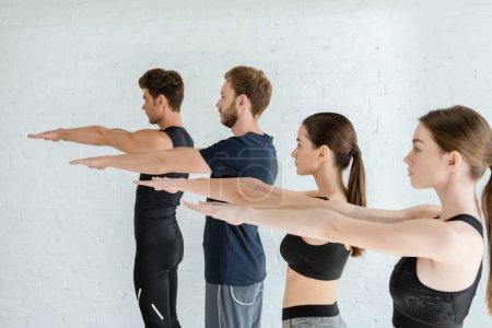 Photo pour Des jeunes en tenue de sport pratiquant le yoga en montagne en posant les mains tendues - image libre de droit
