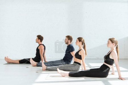 Photo for Young people in sportswear practicing yoga in staff pose - Royalty Free Image