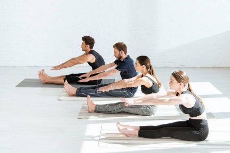 Photo pour Des jeunes en vêtements de sport pratiquant le yoga en position coudée vers l'avant - image libre de droit