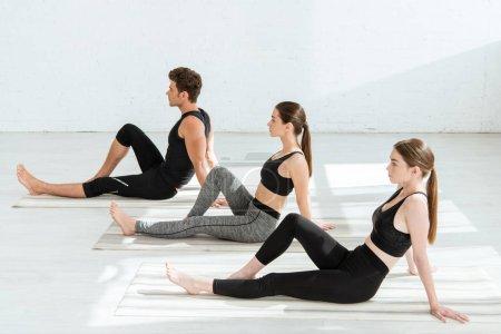 Photo pour Les jeunes femmes et les jeunes hommes qui pratiquent le yoga en cabinet posent avec un genou plié - image libre de droit