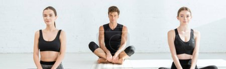 Photo for Panoramic shot of young women and man practicing yoga in half lotus pose - Royalty Free Image