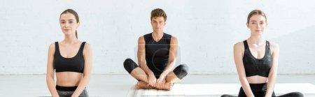 Photo pour Plan panoramique de jeunes femmes et l'homme pratiquant le yoga en demi-lotus pose - image libre de droit