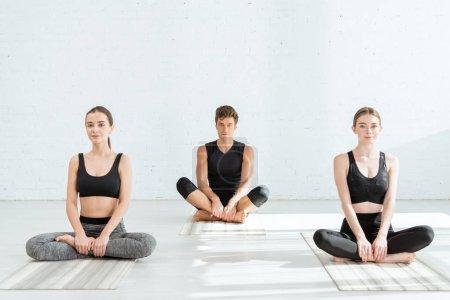 Photo pour Les jeunes femmes et les jeunes hommes qui pratiquent le yoga en demi-lotus posent - image libre de droit