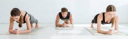 Photo pour Photo panoramique de jeunes femmes et hommes pratiquant le yoga en pose de planches d'avant-bras - image libre de droit