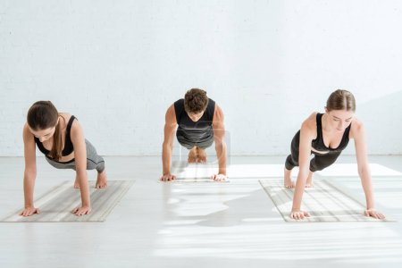Photo for Young women and man practicing yoga in plank pose - Royalty Free Image