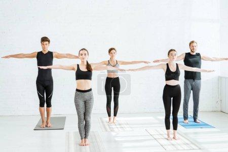 Photo pour Cinq jeunes pratiquant le yoga dans la pose à bras ouverts de montagne - image libre de droit