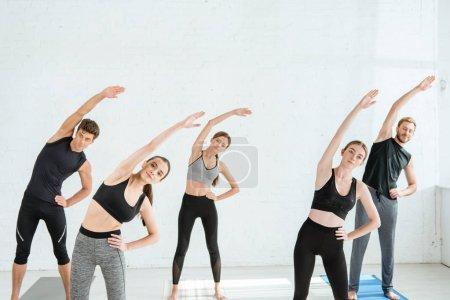 Photo pour Cinq jeunes se penchent latéralement dans une pose d'étoile avec la main sur la hanche - image libre de droit