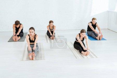 Photo pour Cinq jeunes pratiquant le yoga en flexion avant posent - image libre de droit
