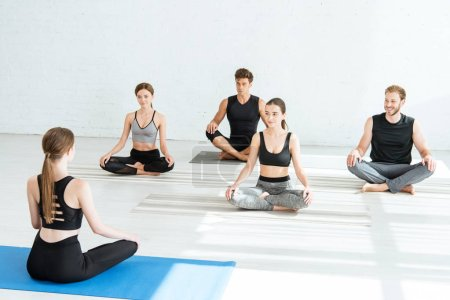Photo pour Back view of yoga instructor showing young people half lotus pose - image libre de droit