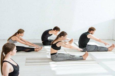 Foto de Cinco jóvenes practicando yoga en una curva sentada hacia delante plantean. - Imagen libre de derechos