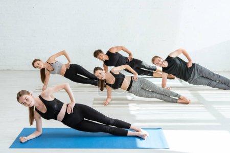 Photo pour Cinq jeunes pratiquant le yoga en pose de planche latérale - image libre de droit
