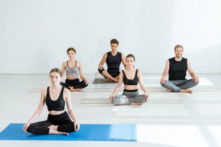 Photo for Five young people practicing yoga in half lotus pose - Royalty Free Image