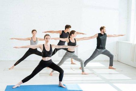 Photo pour Cinq jeunes hommes et femmes pratiquant le yoga en pose de guerrier - image libre de droit