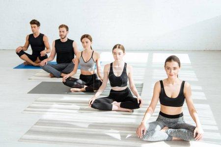 Photo pour Jeunes hommes et femmes pratiquant le yoga en demi-pose de lotus - image libre de droit