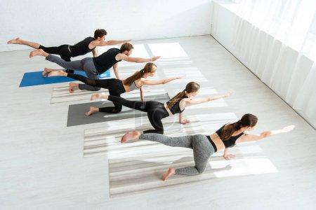 """Photo pour Vue en hauteur de cinq jeunes qui pratiquent le yoga en posant sur une table d """"équilibre - image libre de droit"""
