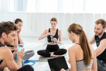 Photo pour Jeune femme utilisant un ordinateur portable près des amis assis dans des poses faciles - image libre de droit
