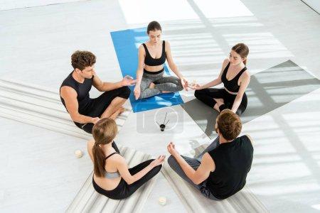 Photo pour Cinq jeunes gens assis en cercle et méditant dans une pose facile près de bougies et de bâtonnets aromatiques - image libre de droit