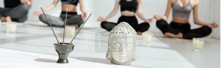 Photo pour Mise au point sélective de têtes de bouddha décoratives, de bâtonnets aromatiques et de bougies, et de jeunes pratiquant le yoga en demi-pose de lotus, plan panoramique - image libre de droit