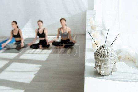 Photo pour La mise au point sélective de la sculpture de la tête de Bouddha avec des bâtons aromatiques sur le rebord de la fenêtre, et trois femmes assises dans la demi-pose de lotus - image libre de droit