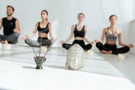 Photo pour L'orientation sélective de la tête de bouddha décorative, des bâtonnets aromatiques et des bougies, et les jeunes pratiquant le yoga en demi-pose de lotus - image libre de droit