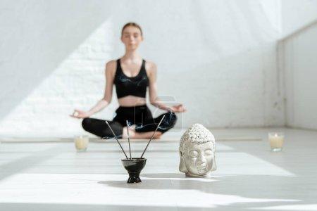 Photo pour Séléction focus of young woman sitting in half lotus pose near buddha head sculpture, aromatic sticks and candles - image libre de droit