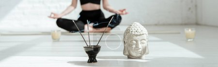 Photo pour Vue en coupe d'une femme assise dans un demi-lotus pose près d'une tête de bouddha sculpture, bâtonnets aromatiques et bougies, photo panoramique - image libre de droit