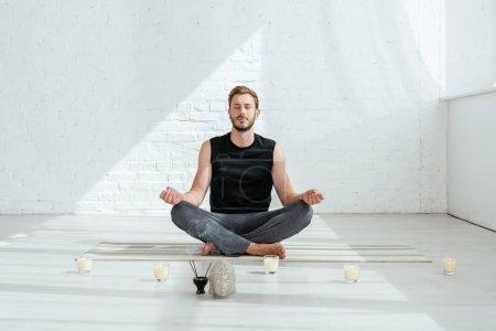 Photo pour Beau jeune homme pratiquant le yoga en demi-lotus pose près de la tête de bouddha décorative, bâtons aromatiques et bougies - image libre de droit