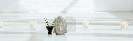 Photo pour Photo panoramique de la tête de bouddha décorative près de bâtonnets aromatiques et de bougies sur fond blanc - image libre de droit