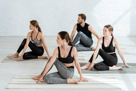 Photo pour Quatre jeunes pratiquant le yoga en demi-colonne vertébrale posent dans le centre sportif - image libre de droit
