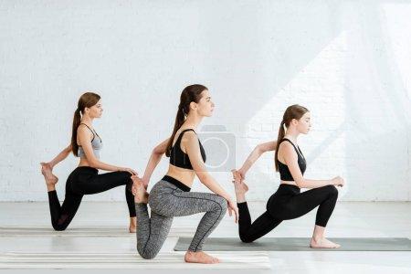 Photo pour Observation de trois jeunes femmes pratiquant le yoga en pose de sirène - image libre de droit
