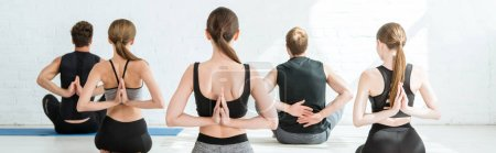 Photo pour Back view of young men and women meditating in thunderbolt pose with prayed hands behind back, panoramic shot - image libre de droit
