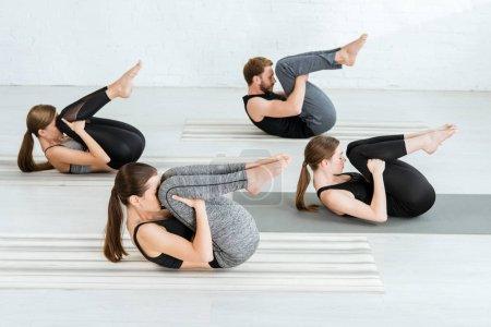 Photo pour Des jeunes en tenue de sport pratiquant le yoga en pose de ballon - image libre de droit