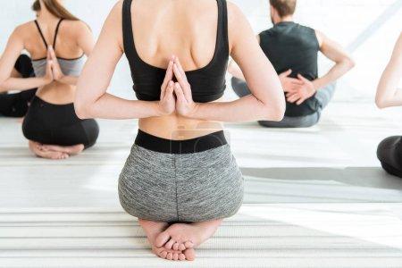 Photo pour Vue arrière des jeunes en vêtements de sport pratiquant le yoga en pose de diamant avec les mains de prière derrière le dos - image libre de droit