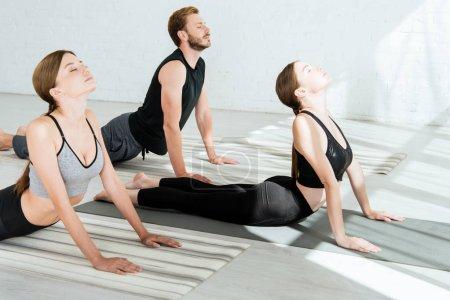 Photo pour Deux jeunes femmes et un homme pratiquant le yoga en pose de cobra élevé - image libre de droit