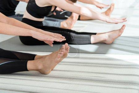 Photo pour Crocheté vue de jeunes en vêtements de sport s'entraînant au yoga en position coudée vers l'avant - image libre de droit