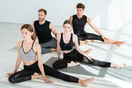 Photo pour Des jeunes en tenue de sport pratiquant le yoga en demi-pose de pigeon - image libre de droit