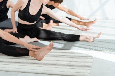 Photo pour Voir les jeunes en tenue de sport s'exercer au yoga en avant se plier pose - image libre de droit