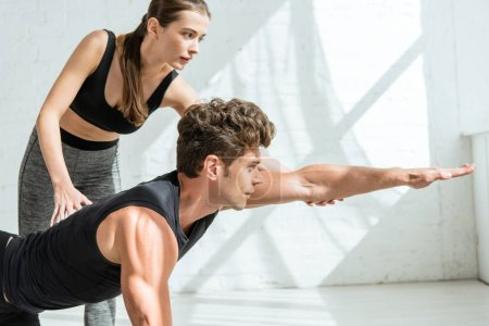 Photo pour Jeune instructeur de yoga jeune instructeur aidant un homme qui pratique le yoga pose - image libre de droit