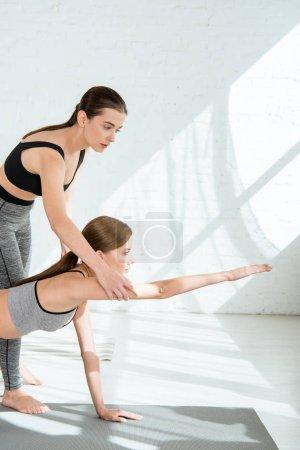 Photo pour Entraîneur attentif aidant les jeunes femmes qui pratiquent le yoga pose - image libre de droit