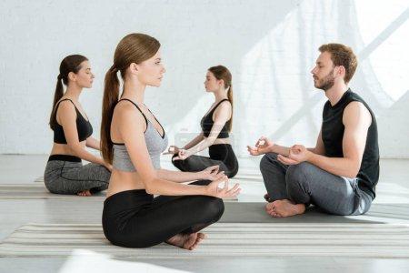 Photo pour Observation de jeunes pratiquant le yoga en demi-lotus pose - image libre de droit