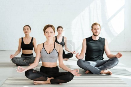 Photo for Front view of young people practicing yoga in half lotus pose - Royalty Free Image