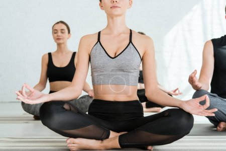 Photo pour Vue recadrée de la jeune femme pratiquant le yoga en demi-lotus pose - image libre de droit