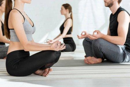Photo pour Vue recadrée des jeunes pratiquant le yoga en demi-lotus pose - image libre de droit