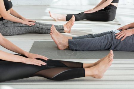 Photo for Cropped view of young people practicing yoga in staff pose - Royalty Free Image